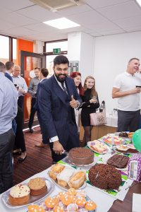 Munday + Cramer's Tayyab Qazi enjoys the cake at this year's Macmillan Coffee Morning