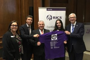 The team presenting a T-Shirt at the Head Office of the Royal Institution of Chartered Surveyors at Parliament Square, London